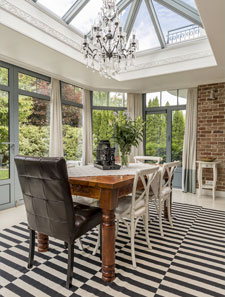 Luxury sunroom addition with floor to ceiling windows, brick wall and chandelier
